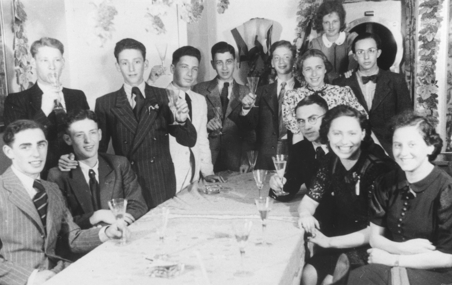 A group of young Jewish refugees raises their glasses in a toast on board the MS St. Louis.  [Probably a celebration held aboard the ship after destinations were found for all the passengers]  Among those pictured are Ilsa Hess (b. Aug. 21,1927 in Frankfurt) on the top of the photo and her sister Vera Hess (b. 1923) on the far right.