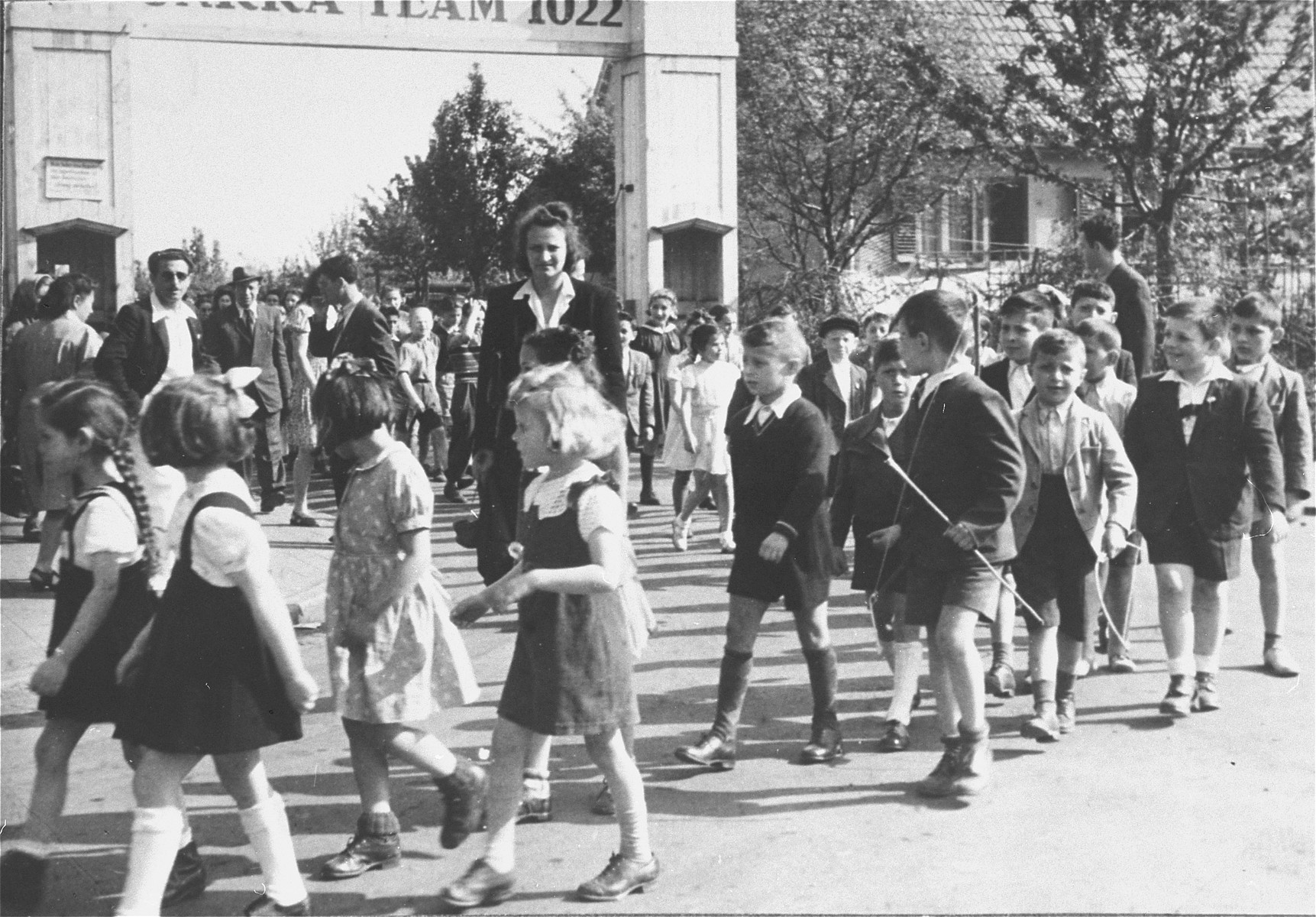 Jewish children walk hand-in-hand through the entrance to the Zeilsheim displaced person's camp during a Lag B'omer festival.