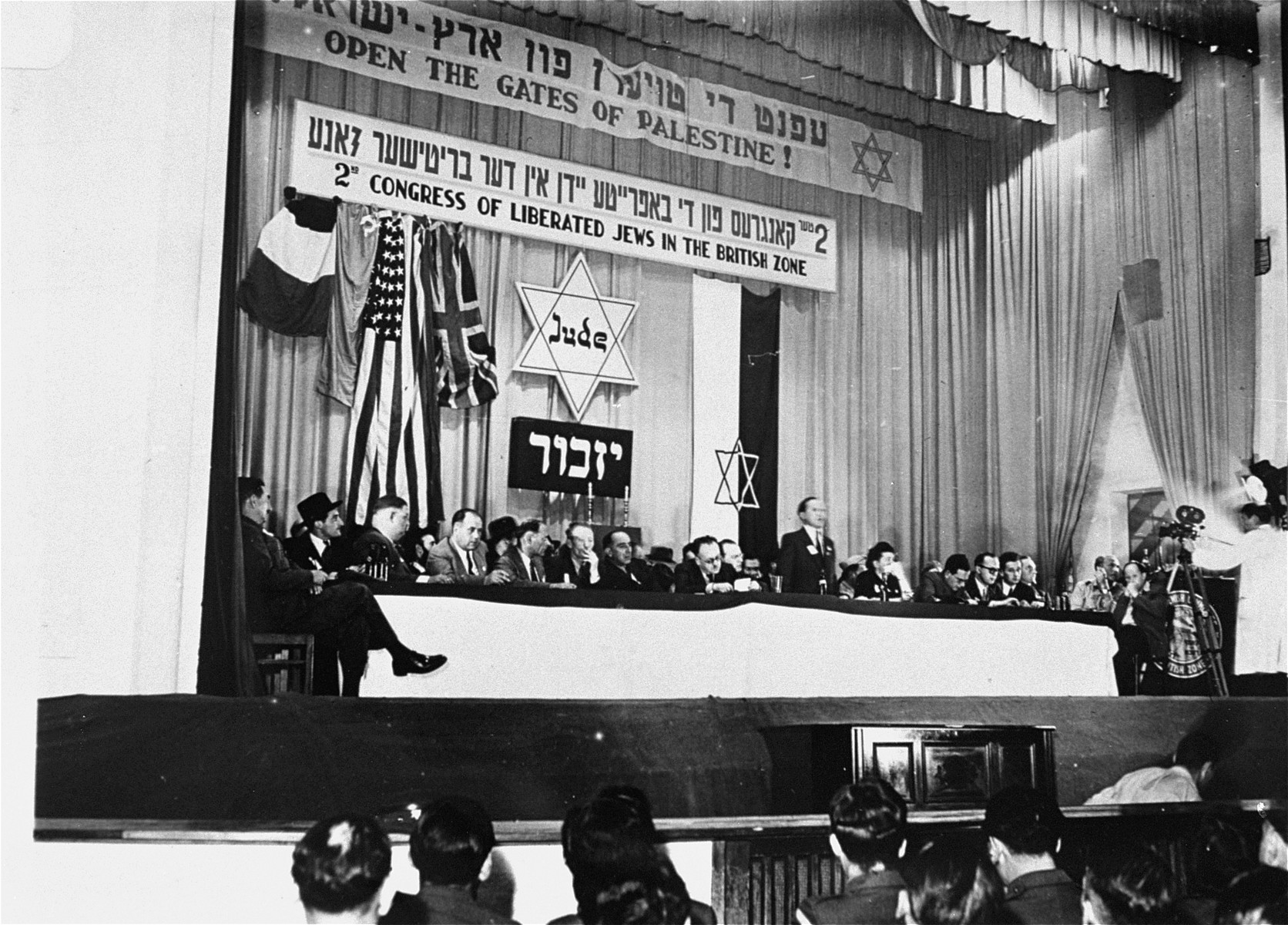 Josef Rosensaft delivers the opening address at the Second Congress of Liberated Jews in the British Zone.  Among those pictured are: Berel Laufer (sixth from the left with a cigarette); Rabbi Helfgott (second from left), Norbert Wollheim (partially obscured); Hadassa (Bimko) Rosensaft (to the right of the speaker); Berel Laufer; David Rosenthal; Pawel Trepman; and Raphael Olewski.