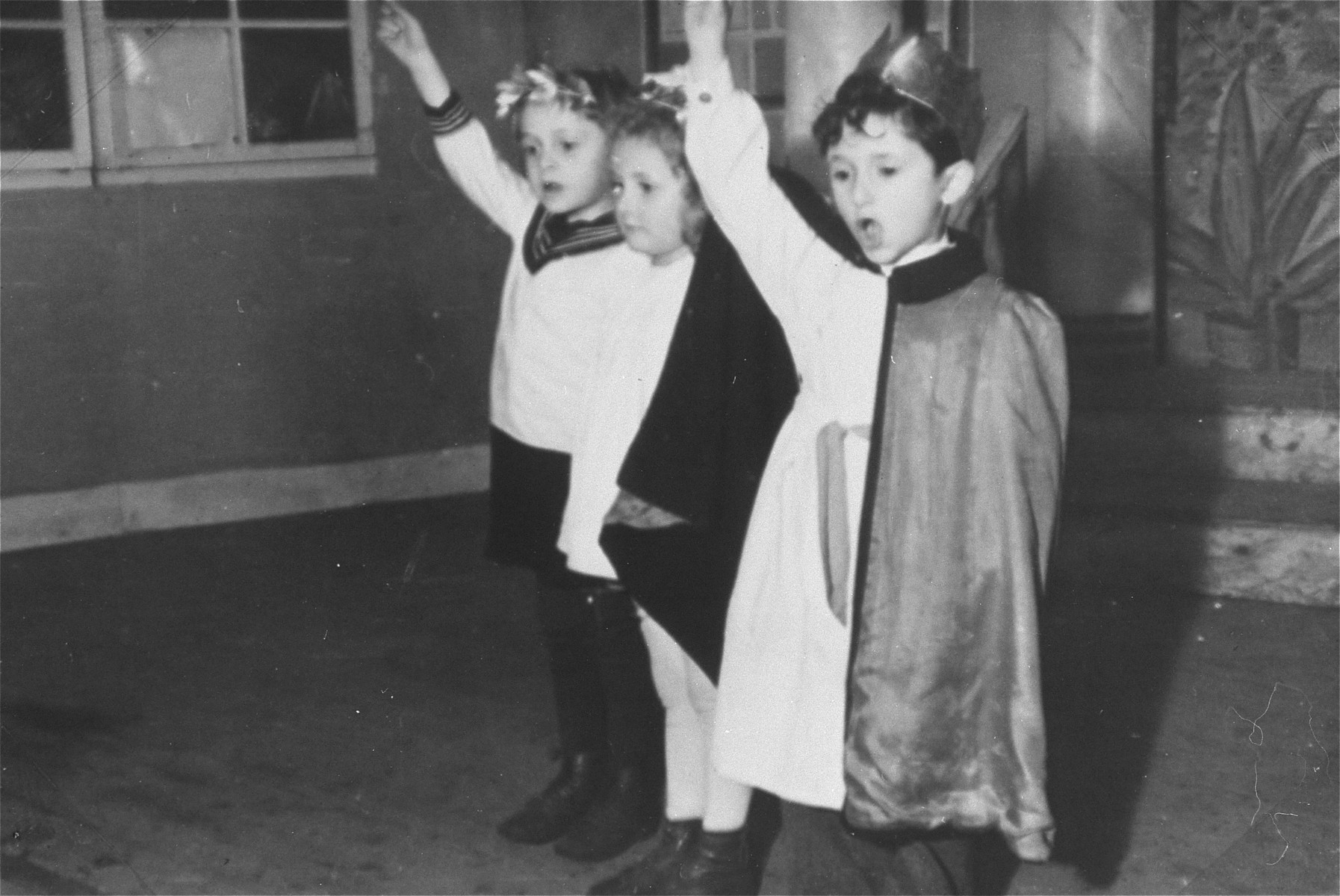 Three young children perform in a Purim show in the Zeilsheim displaced persons' camp.