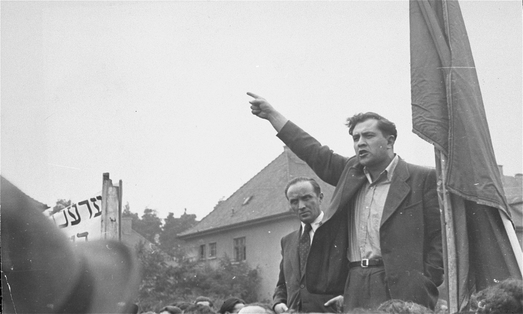 An unidentified speaker addresses the crowd at the Bergen Belsen displaced persons camp during a demonstration protesting the return of the Exodus 1947 passengers to Germany.    Behind the speaker stands Josef  Rosensaft, chairman of the Central Jewish Committee for the British Zone.