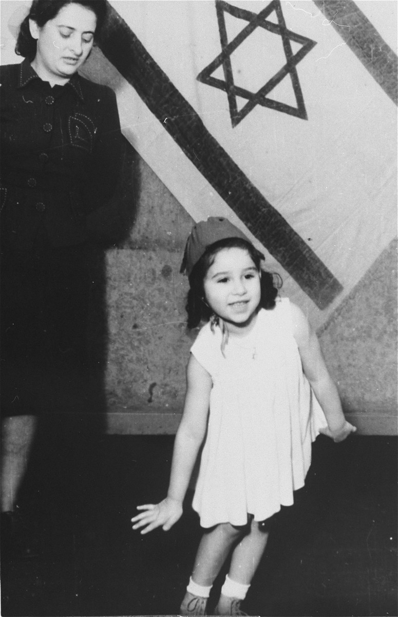 A young girl performs in front of an Israeli flag during a children's ballet performance in the Zeilsheim displaced persons' camp.