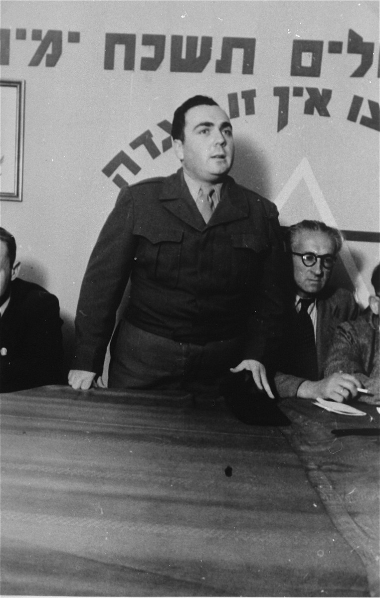 """UNRRA director addresses a group in the Zeilsheim displaced persons' camp.   Zionist slogans are written behind him on the wall: """"If I forget thee O' Jerusalem, may my right hand lose its cunning"""" and If you will it [a Jewish state] it is no dream."""""""