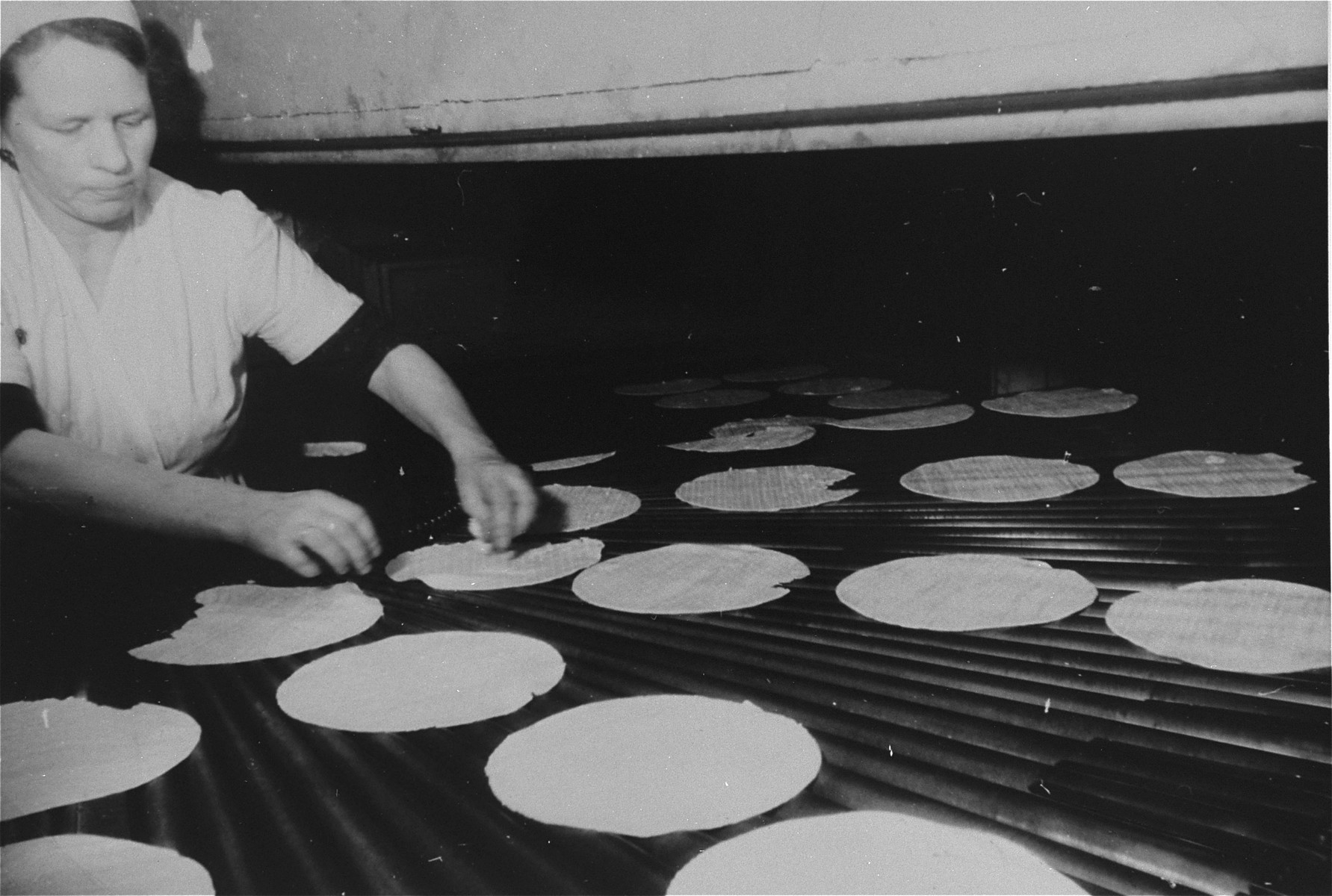 A woman bakes matzah at a bakery in Frankfurt that escaped destruction by the Nazis.