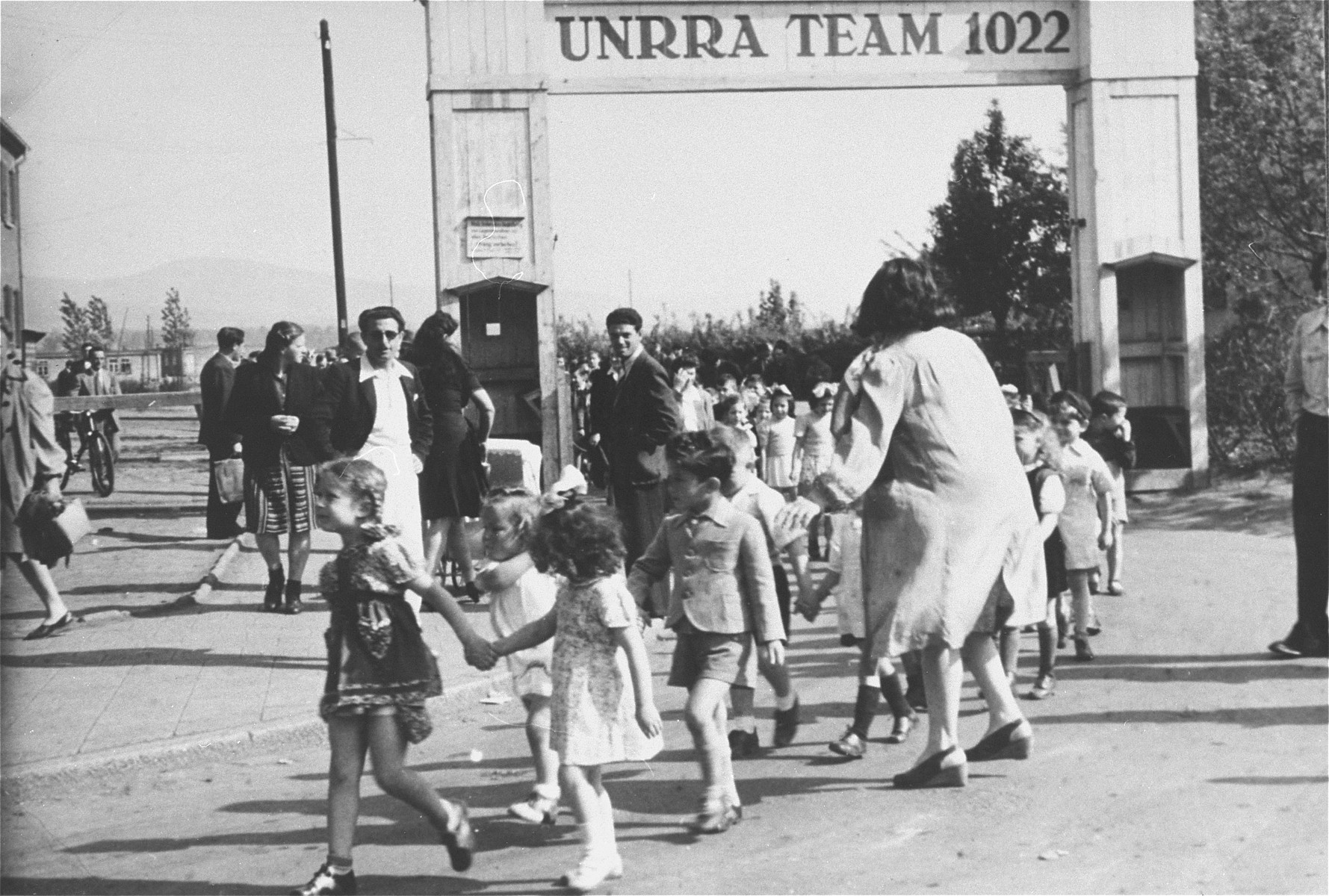 Jewish children walk hand-in-hand through the entrance to the Zeilsheim displaced person's camp during a Lag B'omer festival.   Fay Robinson (in pigtails) leads the children.