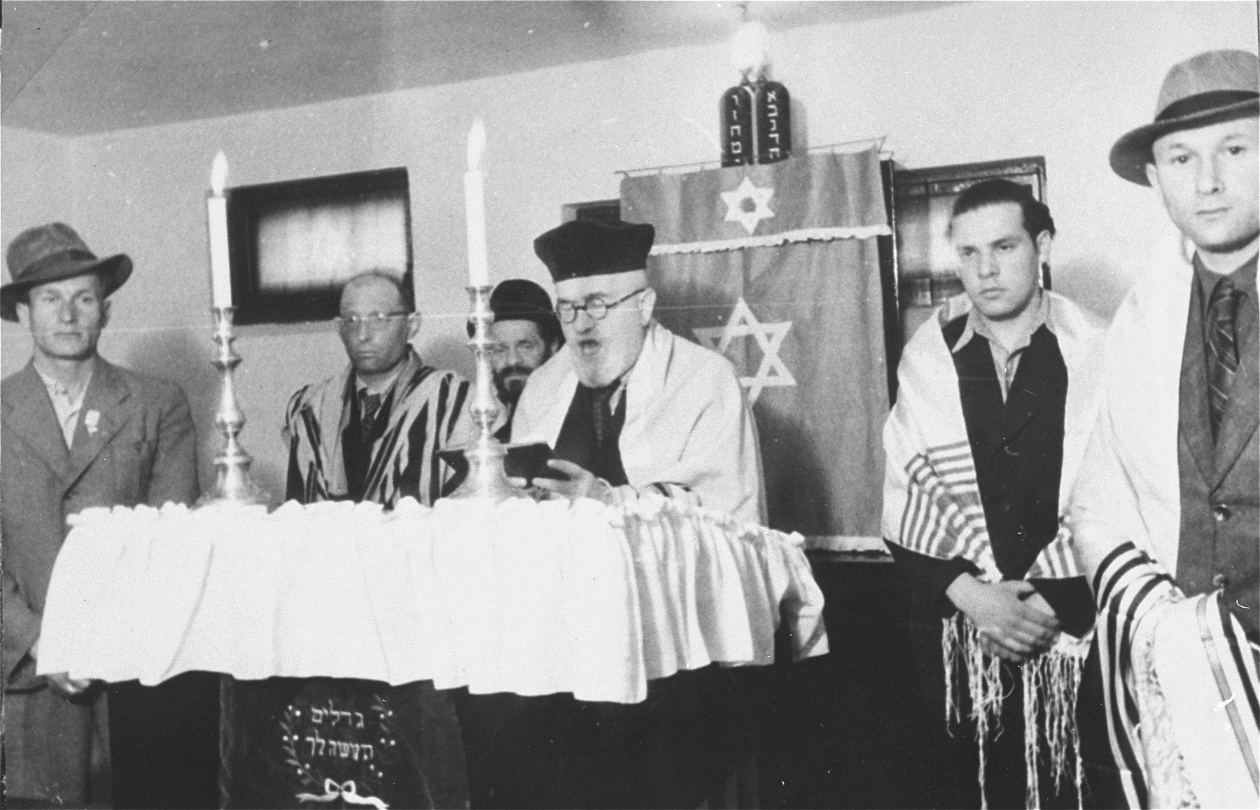 In a synagogue in the Zeilsheim displaced persons' camp, the cantor chants the memorial prayer for victims of the holocaust.  Among those pictured is Roman Bol (Raymond Boll), standing on the far left.