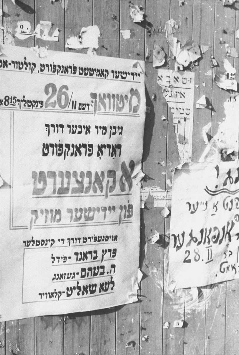 A notice advertising a concert of Yiddish music is posted on a wall in the Zeilsheim displaced persons' camp.  The violinist is Perec Brand.