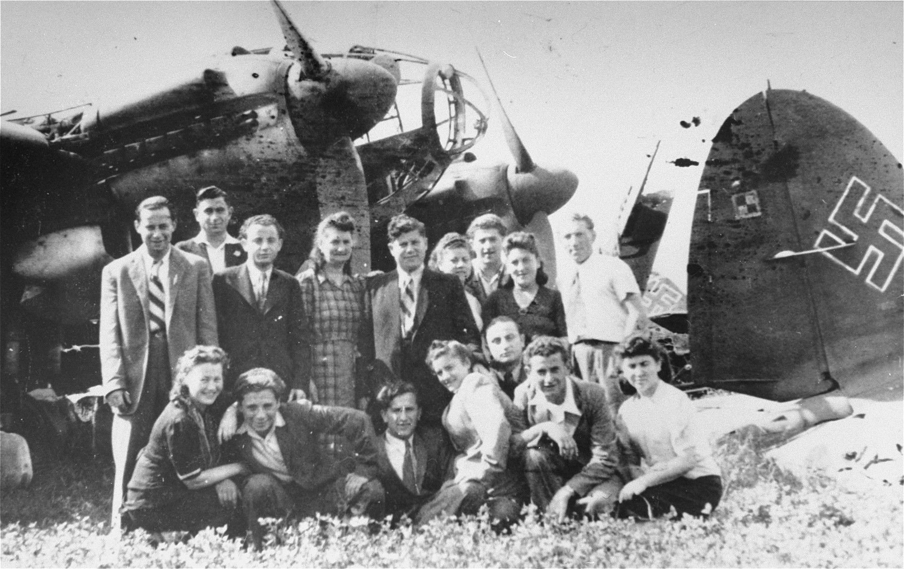 Group portrait of young Jewish DPs in front of a Nazi plane at an airport near Foehrenwald.  Among those pictured is David Bajer (first row, third from the left).
