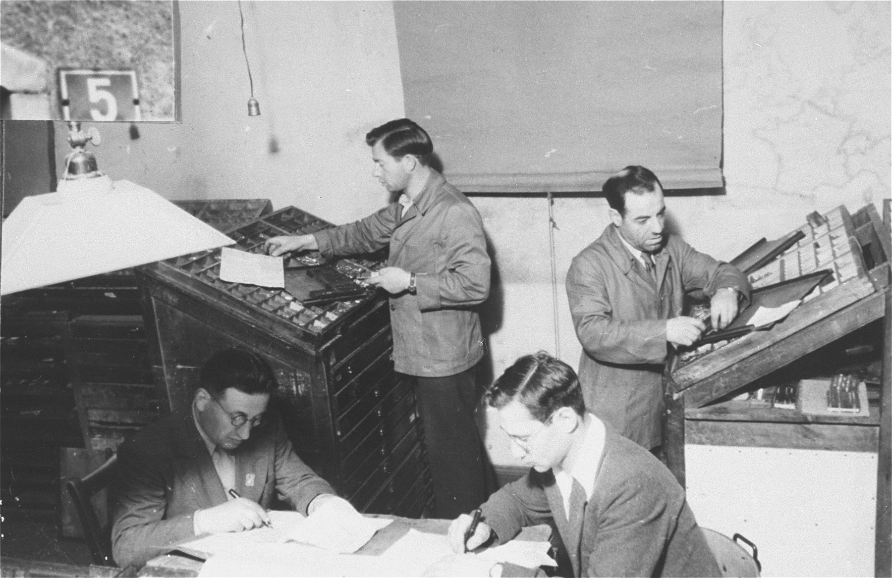 "The staff of the DP newspaper, Unterwegs [The Transient], at work in their office in the Zeilsheim displaced persons' camp.  Unterwegs was first issued under the name Unzer Mut [Our Courage] in November 1946.  It was printed in a typewritten, mimeographed form on poor quality paper.  Edited by Samma Weise, the weekly consisted of ""morale-building"" articles, camp news and gossip, discussions of Jewish problems, and poetry written in Hebrew and Yiddish.  The publishing of ""hard news"" was prohibited by American military and UNRRA regulations."