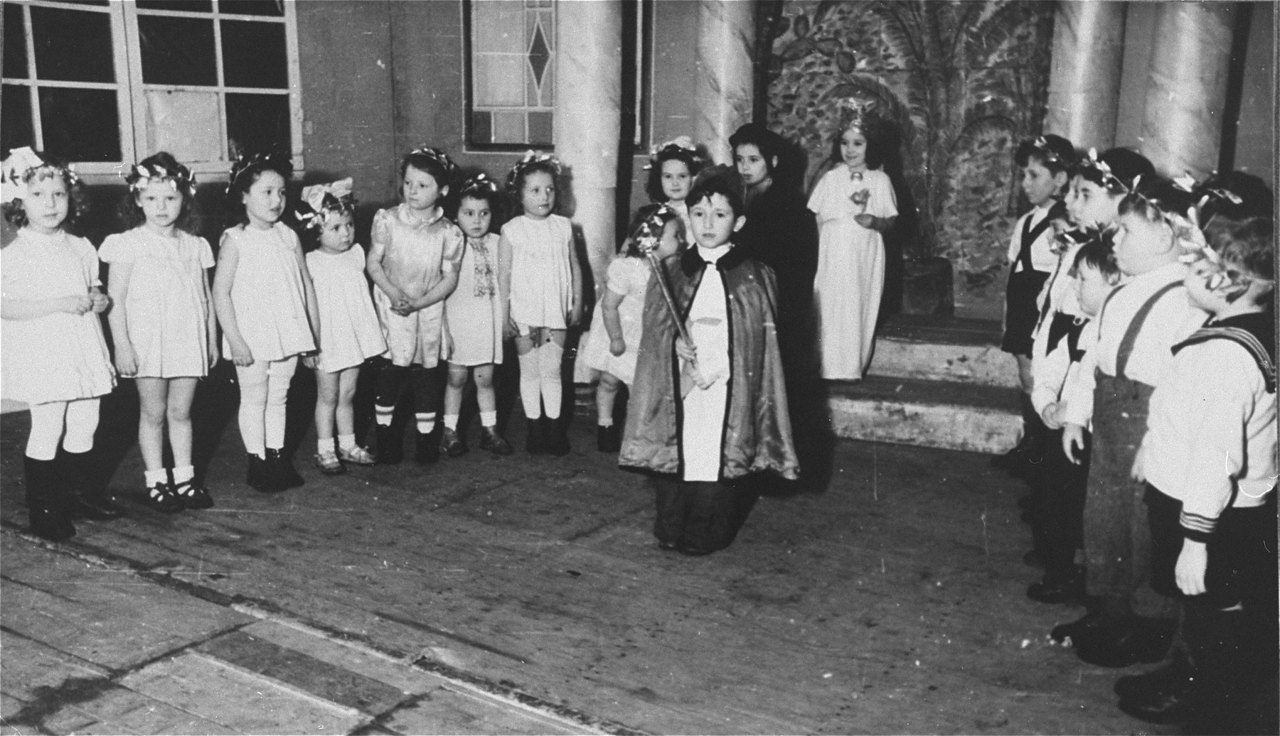 Young children perform in a Purim show in the Zeilsheim displaced person's camp.   Fay Robinson (later Shlimovitz) on the far left, is the daughter of the photographer. She was born July 22, 1941 in Novaya Odessa, Ukraine. She went to Zeilsheim in 1945 and later emigrated to the United States in 1948.