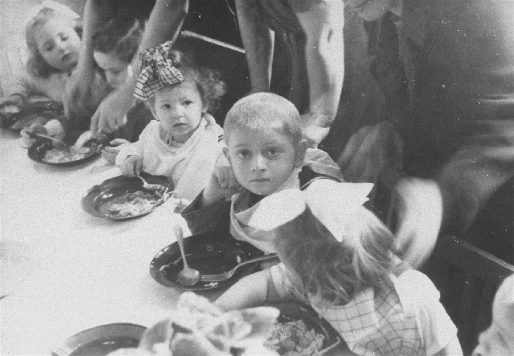 "Young children eat a meal around a table in the preschool of the Zeilsheim displaced person' camp.  The original caption reads: ""In 1946, when the number of children increased, a nursery for preschoolers was organized.""    Among those pictured is Alice Robinson (Rubizon) third child from the left, born February 2, 1945 in Romanovka, Bessarabia."
