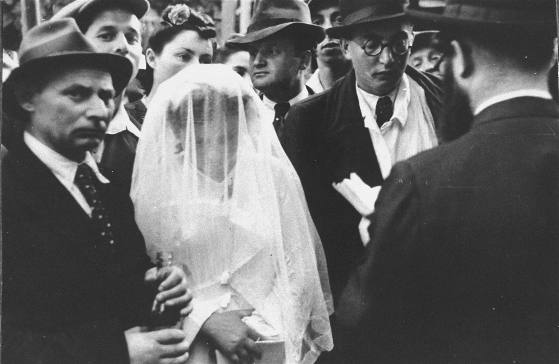 Wedding ceremony at the Zeilsheim displaced persons' camp.  The rabbi recites the marriage blessings under the huppah (canopy).