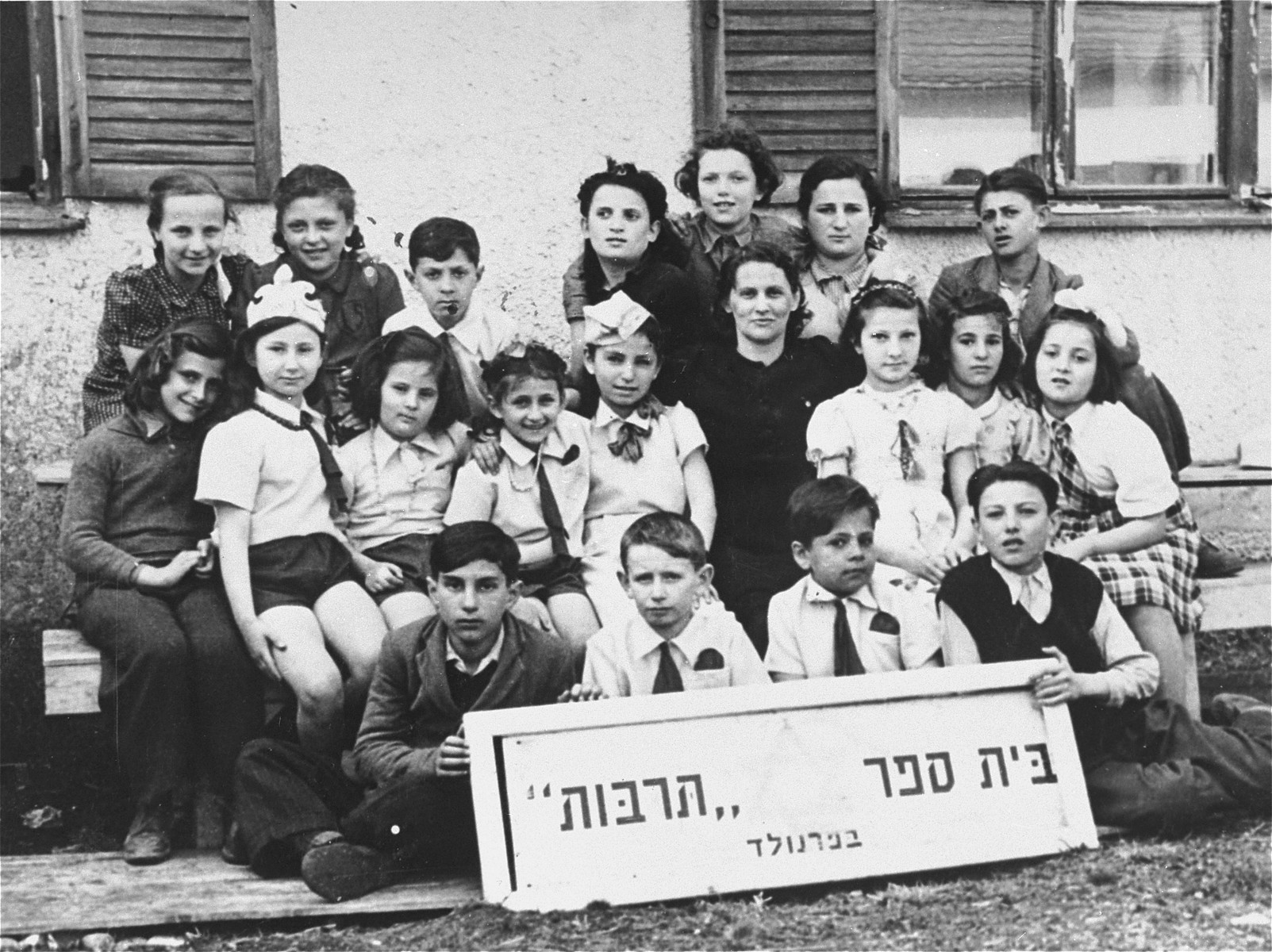 Class photograph of the Tarbut School in the Foehrenwald displaced persons camp.    Pictured in the back row, far right, is Johnny (Yitzhak) Brottman.  Pictured in the second row from left are:  Deborah Korolchuk, Zofja Fajnsztejn, Lucia ?, Esther Kaplan, Chaia Libstug, Mora Ruksin, Roza Saifert and Rosa Li.  In the front row are Bezalel Rottman (front, left) and Paul Brottman (right, holding the sign).