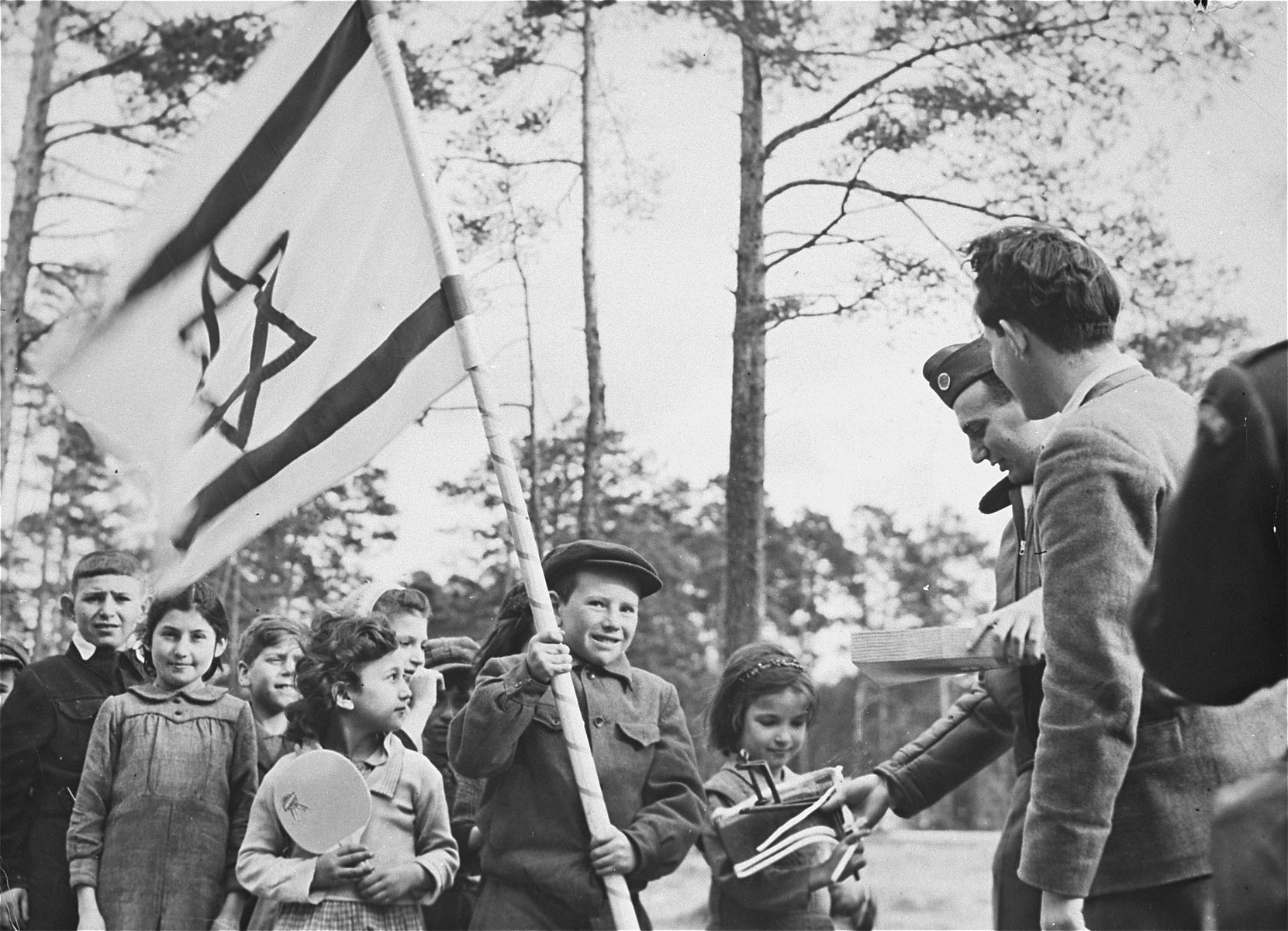 Jewish children at the Foehrenwald DP camp line up while NCWC distributes recreational and educational supplies to the camp members.   Among those pictured are Lilly Swidler (second from the left) and Malka Lancman (now Marlene Stevens) (third from the left).