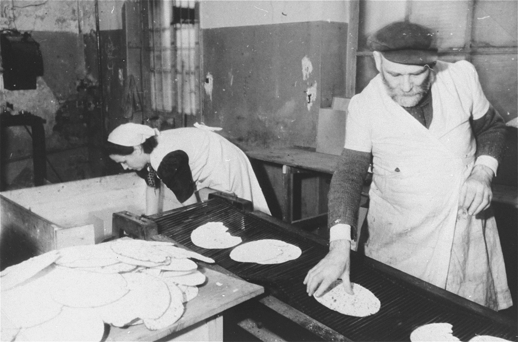 Two workers bake matzah at a bakery in Frankfurt that escaped destruction by the Nazis.