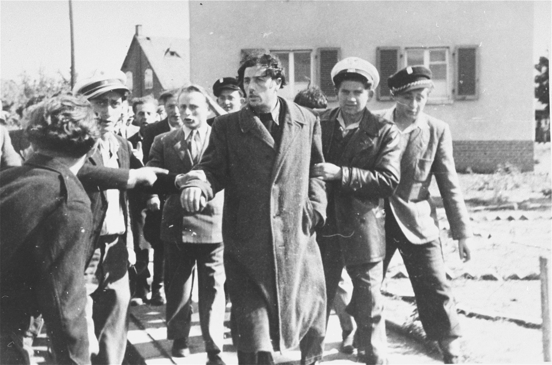 Jewish police detain a former Kapo who was recognized in the street at the Zeilsheim displaced persons' camp.