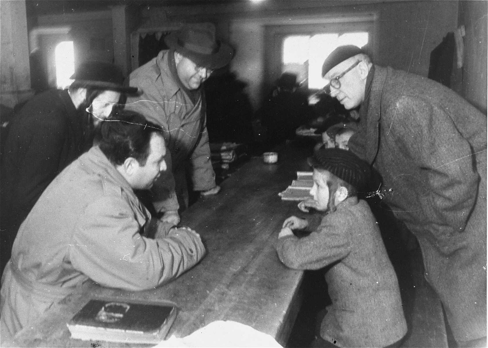 Saul Sorrin (left, foreground), director of UNRRA in the Munich area, visits a heder (religious primary school) at the Foehrenwald DP camp camp in the company of Frank  Kingdon (right), American journalist and politician, and Ted Feder (left), assistant director of the JDC in Germany.