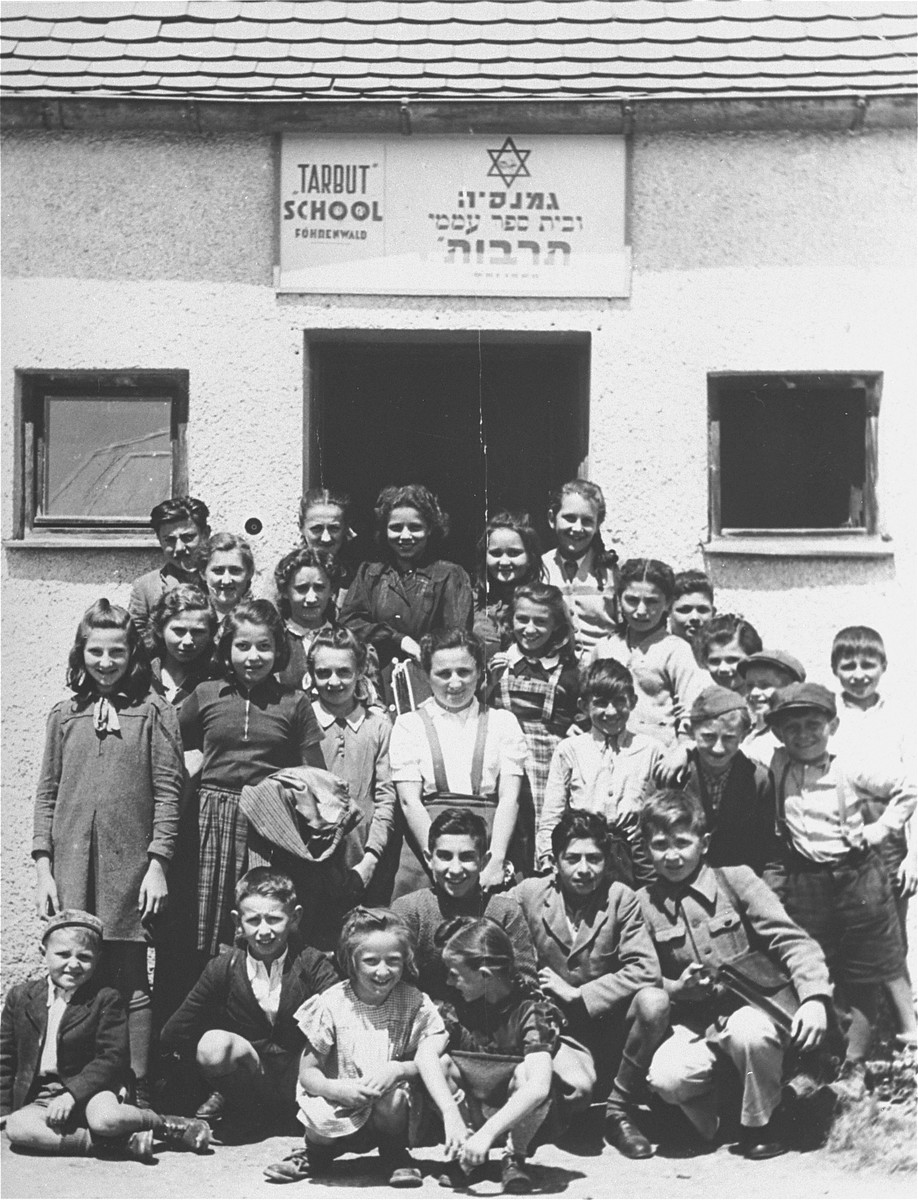 Group portrait of students at the Tarbut school in the Foehrenwald displaced persons camp.     Among those pictured are:  Abraham Burshtain (Bursztyn) (bottom row, far left). Roman Haar (bottom row, far right); Chaya Libstug (third row, third from left) in braids; Pesa Balter (second row from the top, third from the right) and Chaim Swidler (second row from bottom, second from the right).  Paula Lebovics is in the plaid skirt.  Also pictured is Bezalel Rotman.
