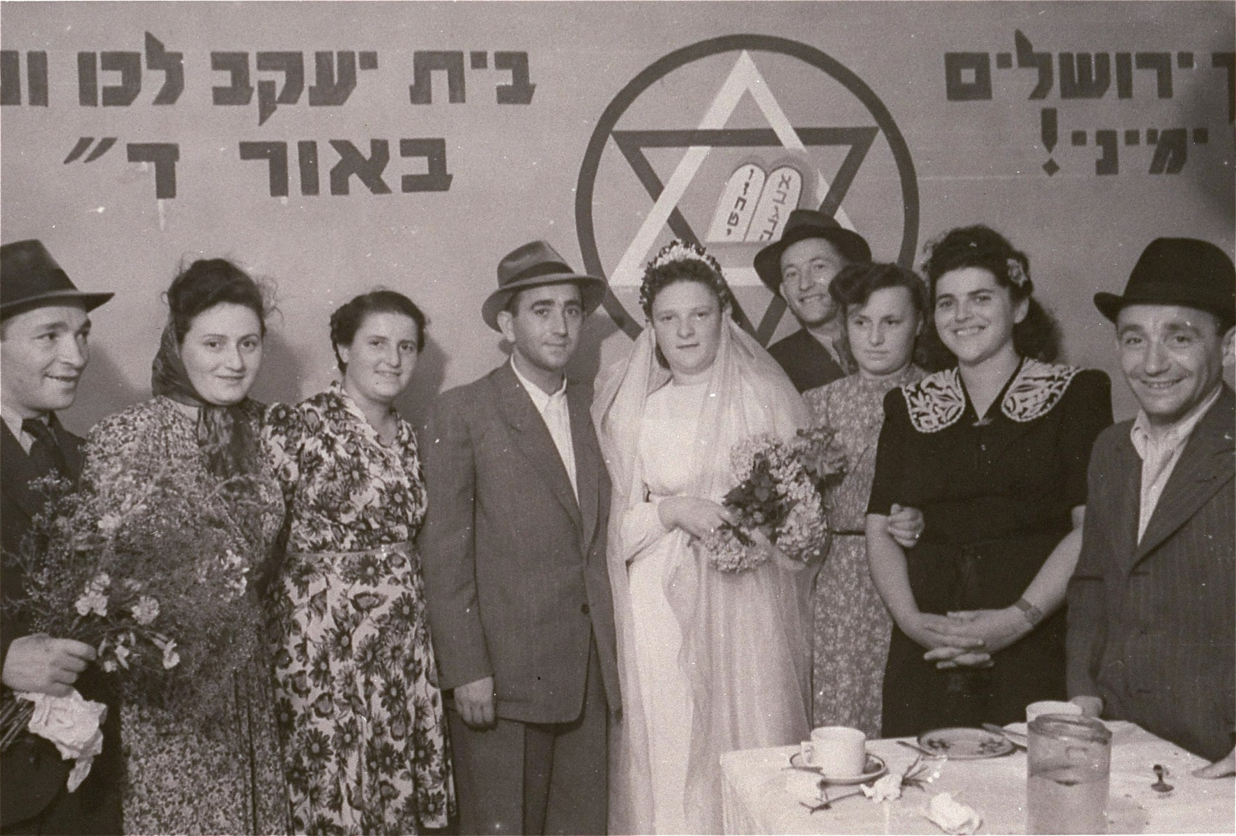 Group portrait of the members of a wedding party at the Zeilsheim displaced persons' camp.   The portrait was taken in front of a large Zionist mural.