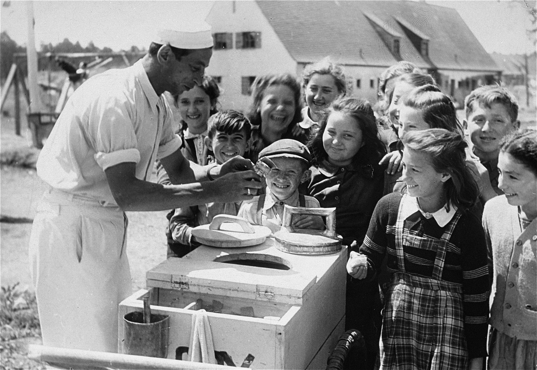 Children wait for ice cream in the Foehrenwald DP camp.    Chaia Libstug is on the extreme right and Nocham Swidler is in the front center.  Paula Lebovics is second from the right in the front.