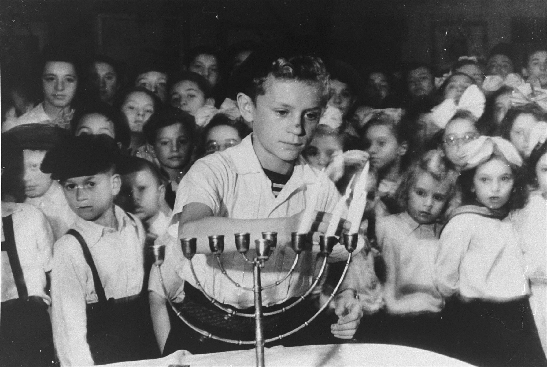 Szlomo Waks, the prize singer of the Children's Center School, lights a Hannukah menorah during a holiday celebration in the Zeilsheim displaced persons' camp.