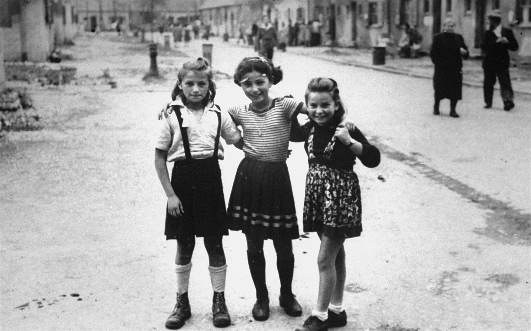 Three young girls pose together on a street of the  Foehrenwald displaced persons camp.    Pictured from left to right are Pesa Balter, Chaia Libstug and Pela Roset.