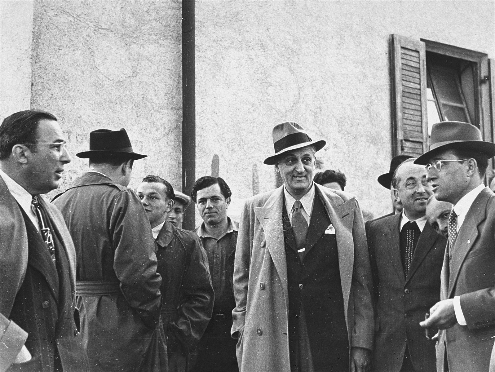 Saul Sorrin (with his back to the camera) director of UNRRA in the Munich area, and Samuel Haber (right) director of the JDC in Germany, converse with American Jews who are on an official visit to the Foehrenwald displaced persons camp.