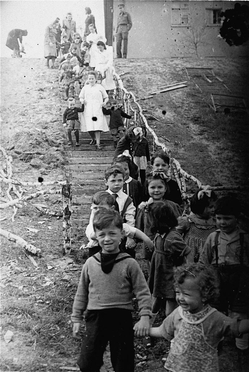 Jewish preschoolers walk down a flight of stairs at the Bergen-Belsen displaced persons camp.  Pictured in front are Sam Richter and his older brother Morris.