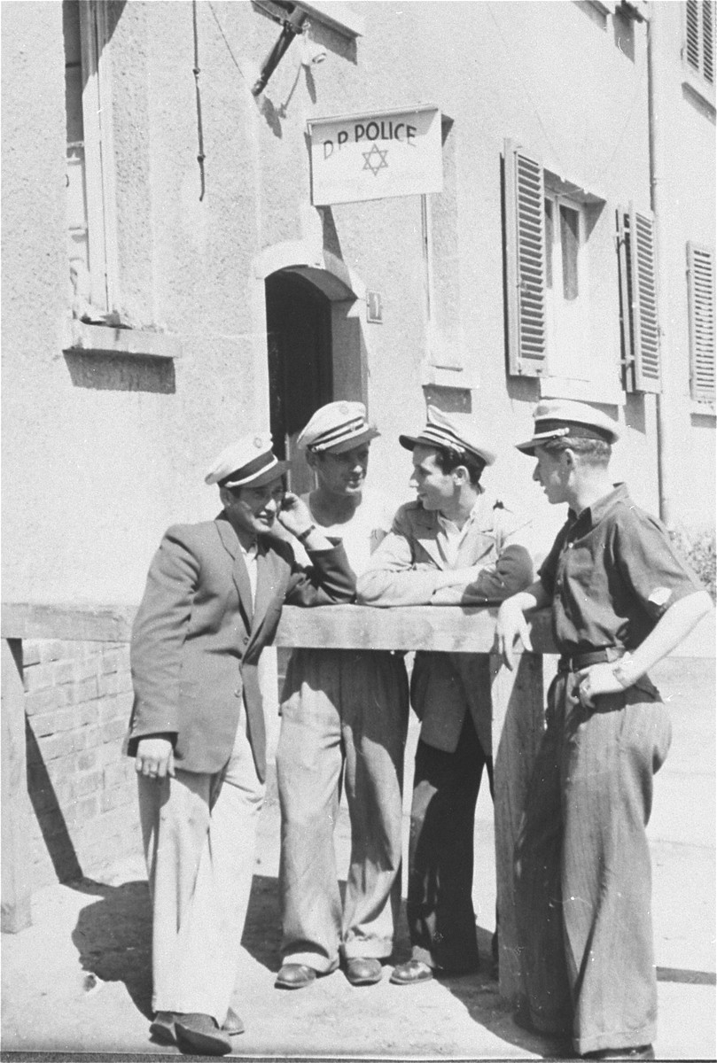 Four Jewish policemen stand outside police headquarters in the Zeilsheim displaced persons' camp.