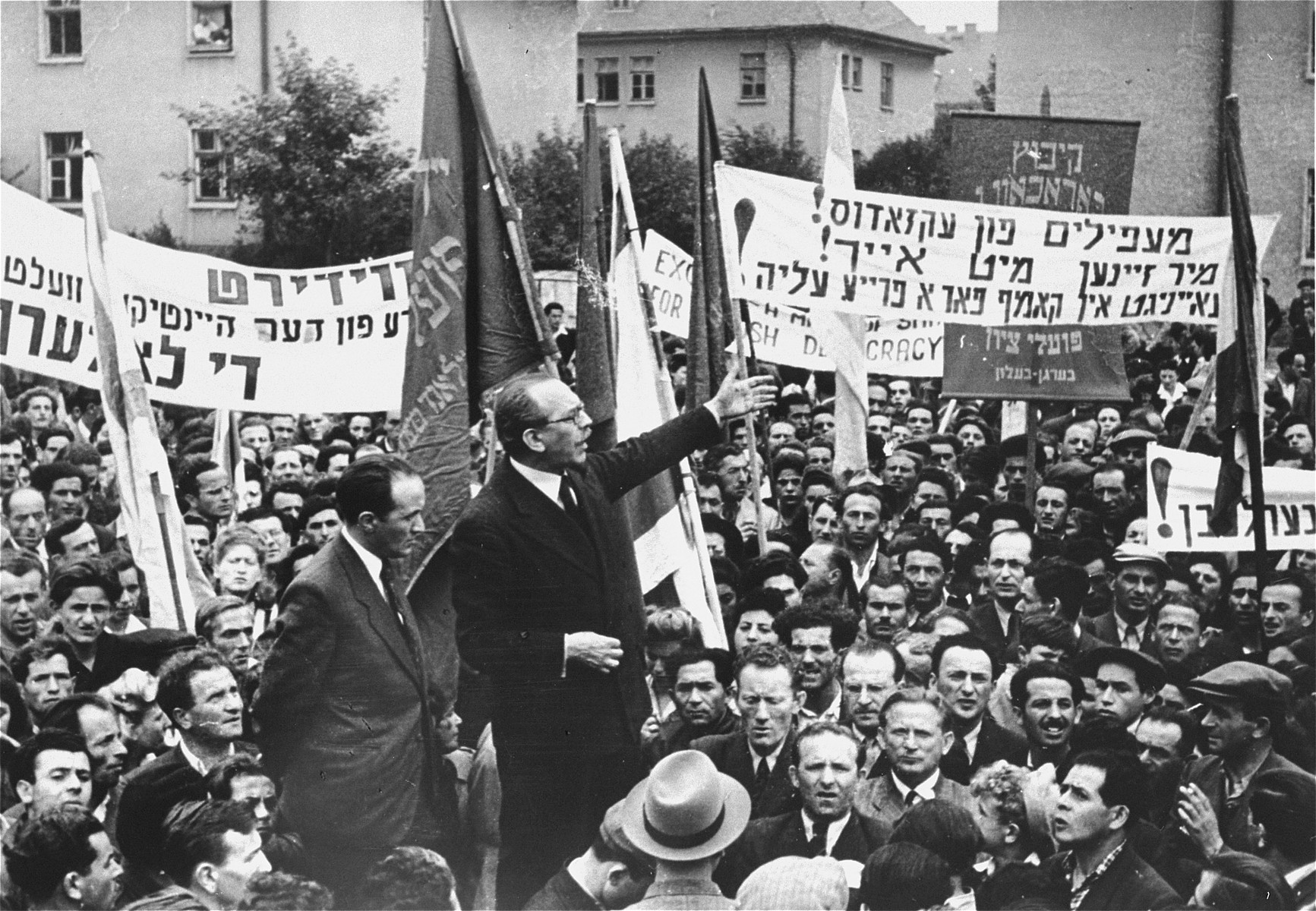 "Marc Jarblum addresses a crowd of DPs at a demonstration protesting the forced return of the Exodus 1947 passengers to Europe.     The Yiddish text of the banner on the right reads:  ""Illegal immigrants from the Exodus we are with you!  United in the struggle for unrestricted immigration!""   Josef Rosensaft stands next to the speaker.  Also pictured are Berel Laufer, Norbert Wollheim, and Max Silbernik.  Josef Rosensaft (1911-1975) was the son of Menachem Mendel and Devora (Szpiro) Rosensaft.  He was born and raised in Bedzin, Poland, where his father, a trained accountant, worked in the family's scrap metal business.  Josef had four older siblings: Chava, Rachel, Mari-Mindl and Itzhak.  His mother died in a flu epidemic when he was eight or nine.  During his youth and early adulthood, Josef was active in the labor Zionist movement.  After he finished school he joined his father in the scrap metal business.  Josef remained in Bedzin during the first four years of the German occupation of Poland.  On June 22, 1943 he was put on a deportation transport to Auschwitz, but managed to escape by diving out of the train into the Vistula River.  Though wounded by German bullets during his escape, Josef made it back to Bedzin the following morning.  A few weeks later during the final liquidation of the ghetto, his father died in his arms of natural causes. Josef then fled to the nearby town of Zawierce to escape the deportations.  However, that same month he was again rounded-up and sent to Auschwitz-Birkenau.  Josef spent five months in the camp before being transferred to the Auschwitz sub-camp of Lagisza Cmentarna in January 1944.  That winter he escaped from the camp and returned to Bedzin, where he was hidden by a Polish friend for six weeks.  He was recaptured in April and sent back to Auschwitz, where he was imprisoned in the Block 11 punishment barracks for seven months.  In November Josef was transferred to the Buchenwald sub-camp of Langensalza, and from there to Dora-Mittelbau early in 1945.  He was moved one last time to Bergen-Belsen in early April, where he was liberated by the British on April 15.  Within days of the liberation, Josef was chosen by his fellow survivors to become chairman of the Bergen-Belsen camp committee.  Later, after the convening of the First Congress of Liberated Jews in the British Zone in September 1945, he was elected chairman of the Central Jewish Committee for the British Zone of Germany.  He headed both the camp committee and the central committee until the closing of the Bergen-Belsen displaced persons camp in the summer of 1950.  During his years of leadership in the DP community Josef repeatedly stood up to the British in defense of the needs and political sensitivities of Jewish survivors.  He demanded that the British formally recognize Jews as a separate category of displaced persons.  He halted the transfer of Belsen DPs to two inferior camps established near the Dutch border.  He thwarted the British attempt to change the name of the Belsen DP camp to Hohne, which would have diminished the moral and political power of the DPs living there that derived from their link to the infamous concentration camp.  Finally, he repeatedly spoke out against the anti-Zionist policies of the British government and actively aided the illegal Bricha and Aliyah Bet movements that strove to get Jews out of Eastern Europe and smuggle them into Palestine.  On August 18, 1946 Josef Rosensaft married Hadassah Bimko (1912-1997), a fellow Bergen-Belsen survivor from Sosnowiec, Poland, who at the time was head of the health department of the Central Jewish Committee in the British Zone.  Hadassah was the daughter of Hersh Leib and Hendla Bimko, Gerer Hasidim who worked in the jewelry manufacturing business.  She had a younger brother, Benjamin and a younger sister, Roszka.  In the summer of 1943 Hadassah was deported to Auschwitz-Birkenau, where she spent fifteen months before being transferred to Bergen-Belsen in November 1944.  While she survived, most of her relatives, including her husband, son, parents and sister, perished in Auschwitz.  A dentist by training who had also studied medicine, Hadassah was recruited immediately after the liberation to organize a group of Jewish doctors and nurses in the camp to help British medical personnel treat the thousands of Belsen survivors suffering from disease and malnutrition.  Hadassah also served as one of the principal prosecution witnesses at the Bergen-Belsen Trial in Lueneburg (September-November 1945).  A year-and-a-half after their marriage, Hadassah gave birth to their son Menachem on May 1, 1948.  With the closing of the Belsen DP camp, the Rosensafts moved to Switzerland, where they spent eight years in the town of Montreux.  The family then immigrated to the United States, where Josef remained active in a variety of Jewish organizations.  He served as president of the World Federation of Bergen-Belsen Survivors until his death."