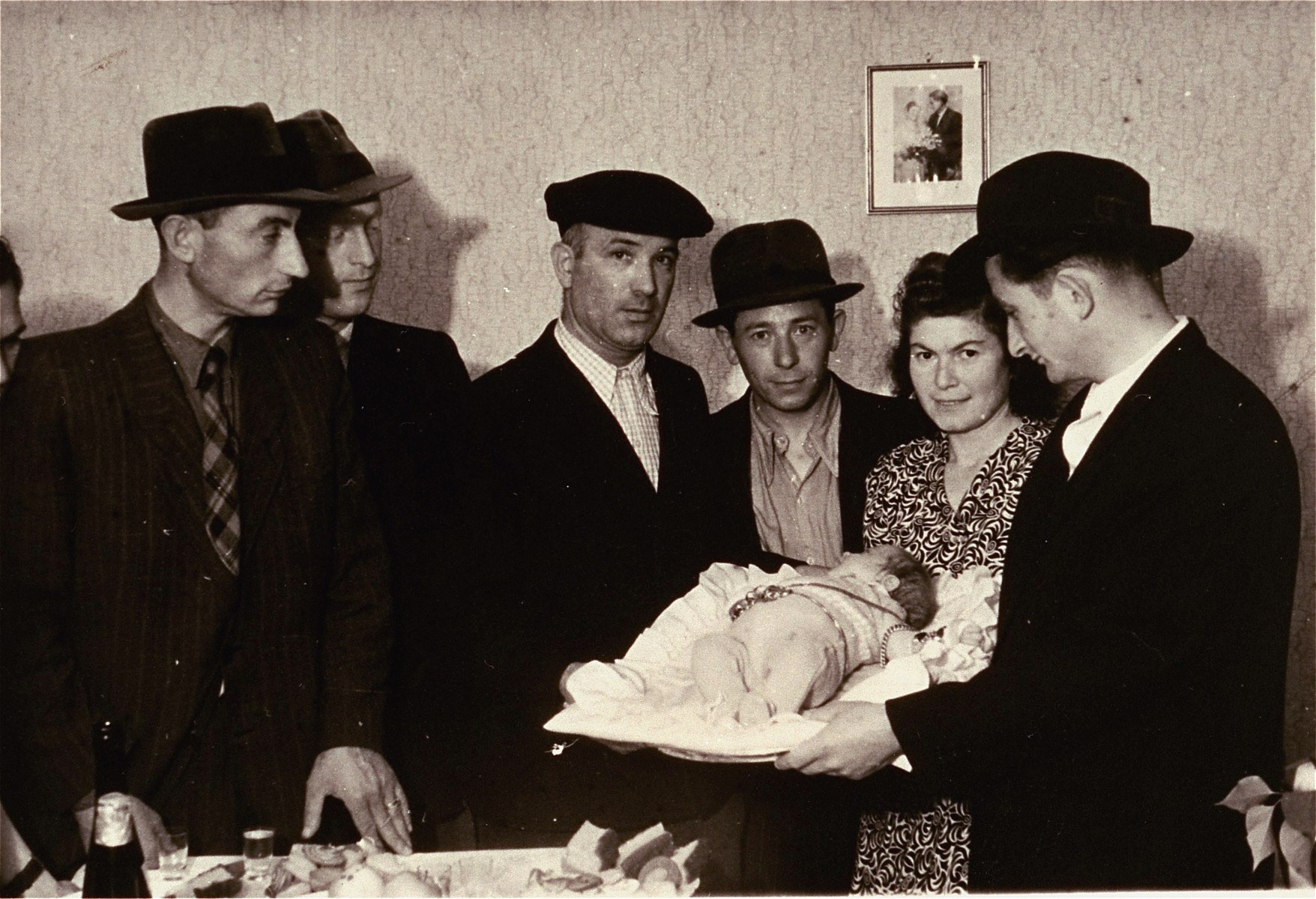 A family of Jewish DPs poses with their newborn at a circumcision ceremony in the Zeilsheim displaced persons camp.