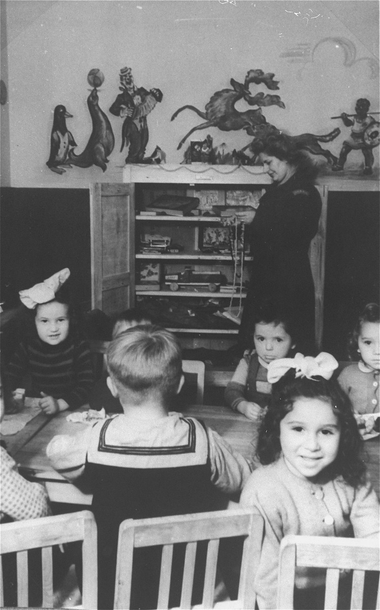 """Young children sit around a table in the nursery school of the Zeilsheim displaced persons' camp.  The original caption reads: """"In 1946, when the number of children increased, a nursery for preschoolers was organized."""""""