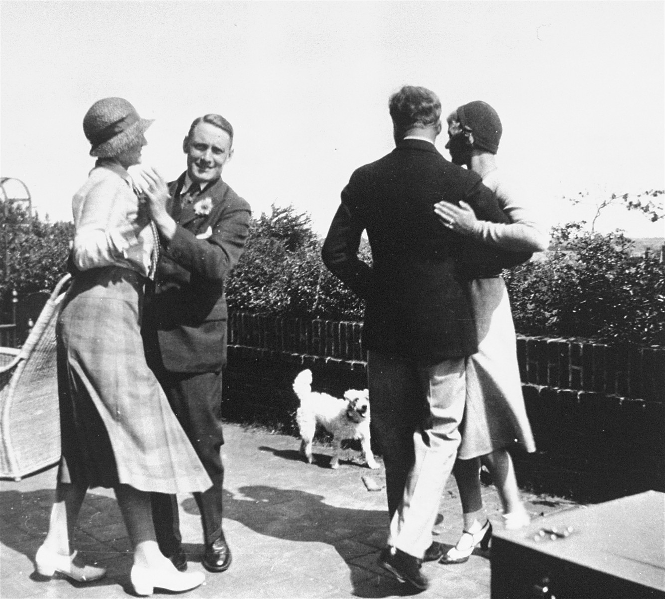 Willem Arondeus (left) and writer A. Roland Holst (right) dancing at a garden party.    Later during the war, Arondeus led a gay resistance group in Amsterdam that was responsible for bombing the Amsterdam Population Registry offices.  The bombing was carried out in an effort to destroy government records on Jews and others sought by the Nazis.  As a result of the act, Arondeus was executed in 1943.  His efforts as a rescuer have been recognized by Yad Vashem and the USHMM.