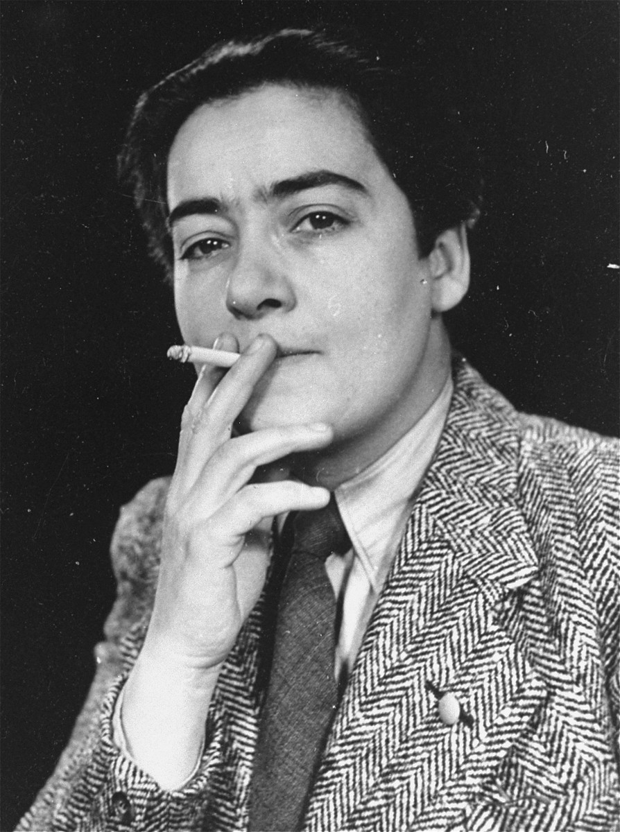 Portrait of Frieda Belinfante, reportedly dressed in men's clothing to disguise herself from Nazi informers.  Belinfante was a half-Jewish lesbian member of a gay resistance group called the CKC.  She participated in the planning of the destruction of the Amsterdam Population Registry in March 1943, and was also active in falsifying identity cards and arranging hiding places for Jews and others sought by the Nazis.  In December 1943, Belinfante escaped to Switzerland via Belgium and France.  After the war, she returned briefly to Amsterdam and then emigrated to the United States.
