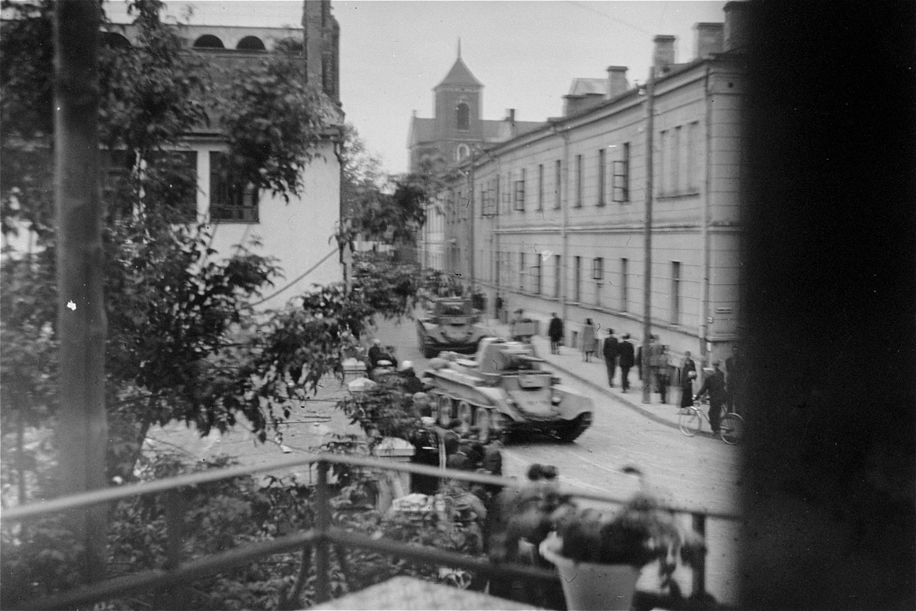 Russian tanks roll through the streets of Kaunas during the Soviet occupation of Lithuania.    This photo was taken through a hole in a piece of paper that was used to cover a window.