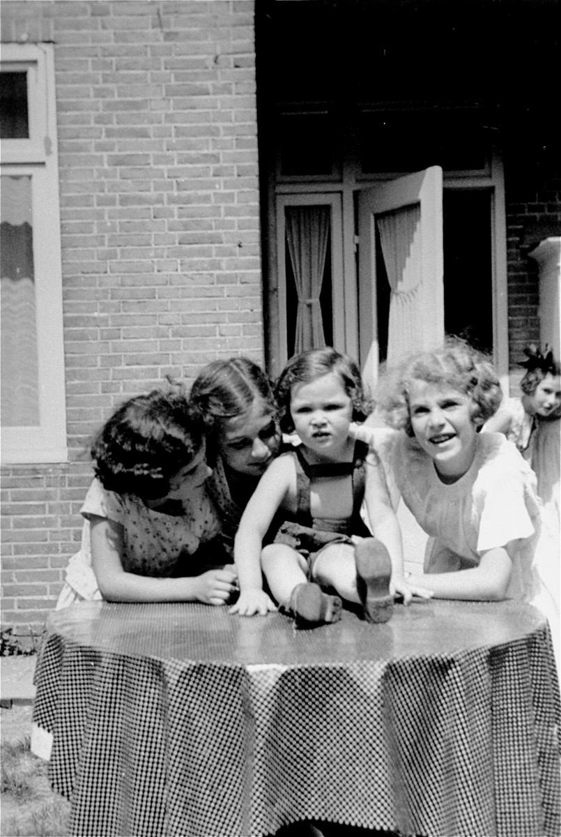 A group of young German Jewish refugee girls pose outside on a terrace in Amsterdam.    Pictured from left to right are: Susanna Ledermann, Dolly Zeetroon, Hannah Toby, Barbara Ledermann and Hanneli Pick-Goslar (at the far right in the background).