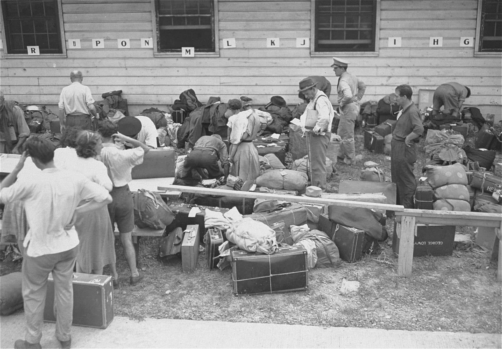 Newly arrived refugees are checked in at the Fort Ontario shelter by representatives of the War Relocation Authority and the U.S. Army; baggage is inspected by U.S. customs officials.