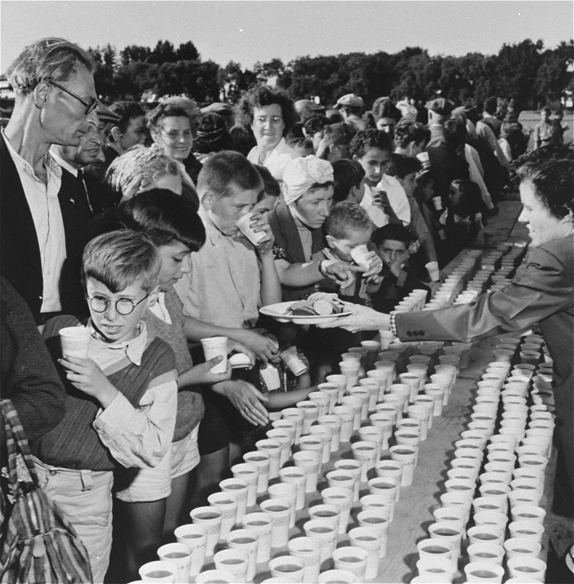 Newly arrived refugees receive food and drink at a picnic at Fort Ontario in Oswego, New York.