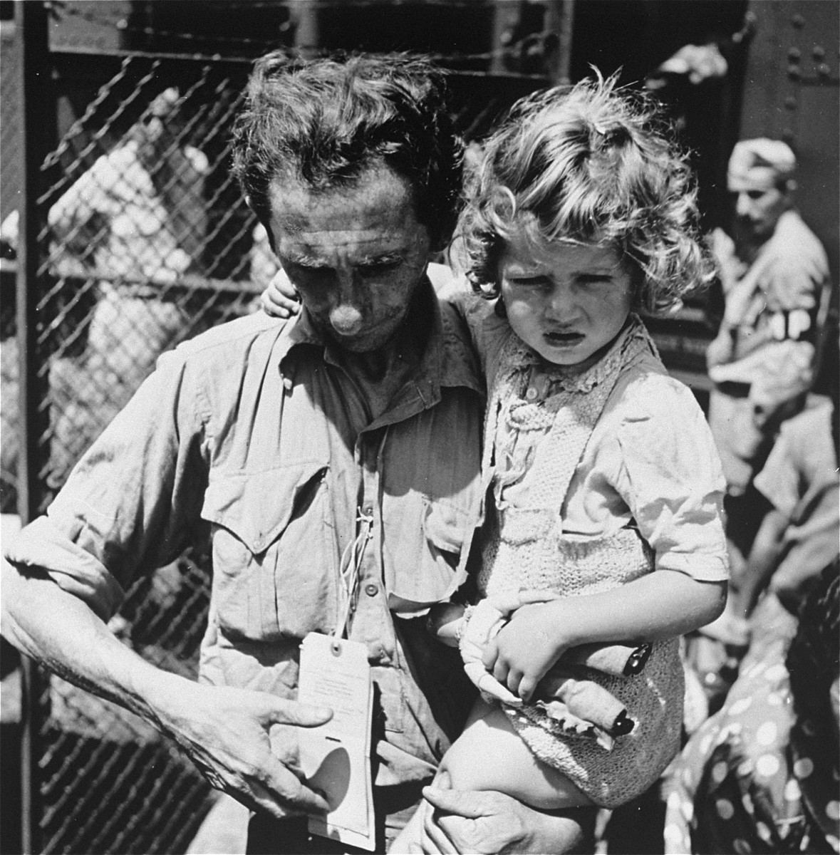 A father, holding his daughter, checks his tags during check in at the Fort Ontario refugee shelter.