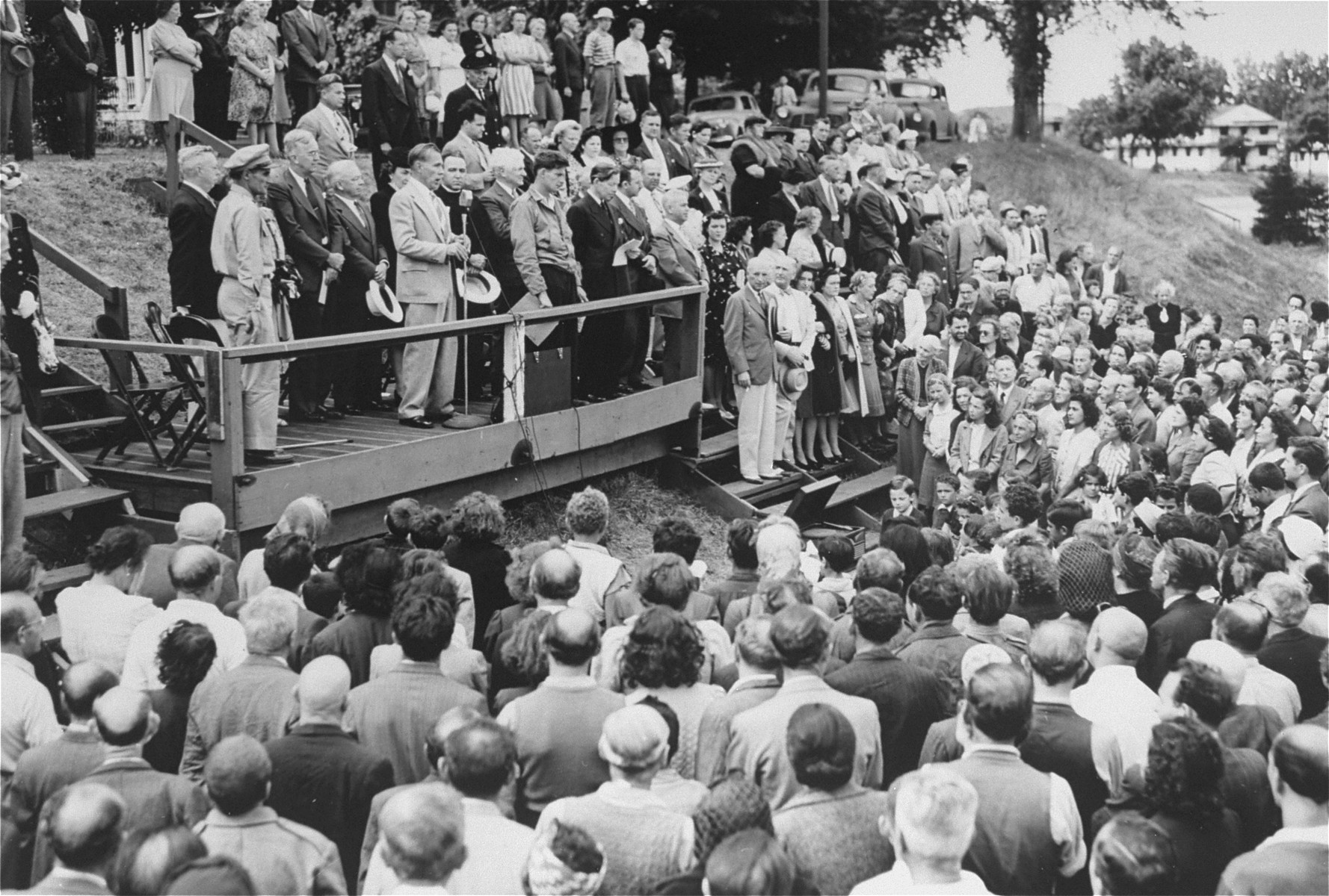 The day after their arrival at Fort Ontario Father J.J. Davem pronounces an invocation at a welcome ceremony for the European refugees.  Among those pictured are Zdenka Levi's brother from Yugoslavia, and Fred Baum, the camp interpreter.