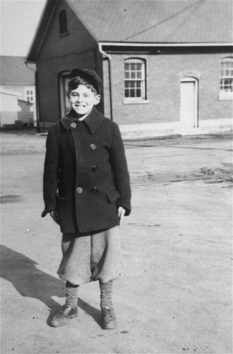 12-year-old Zigmund Krauthamer poses in front of a barracks at the Fort Ontario emergency refugee shelter.