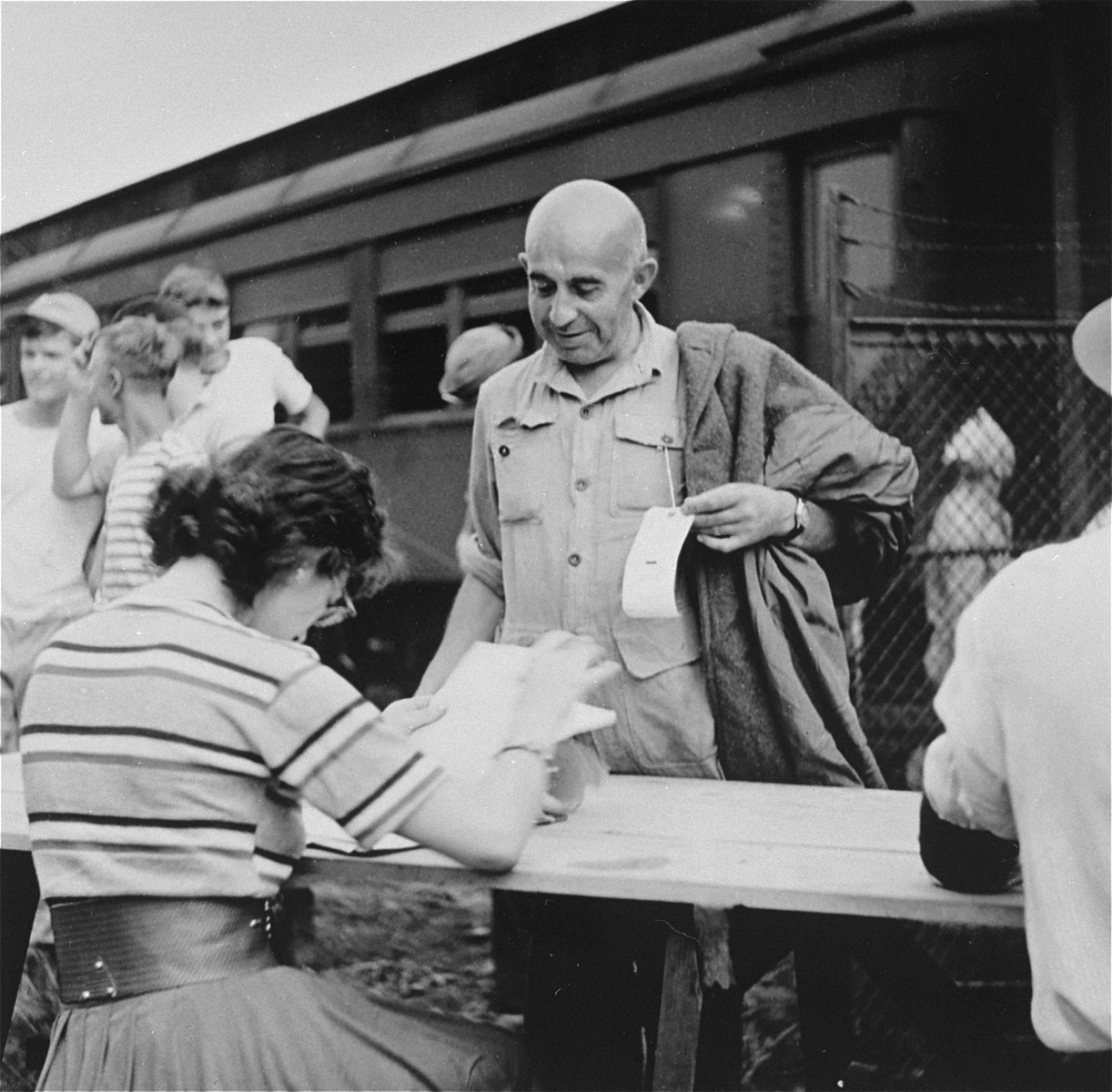 Newly arriving refugees are checked in at the Fort Ontario shelter by representatives of the War Relocation Authority and the U.S. Army.