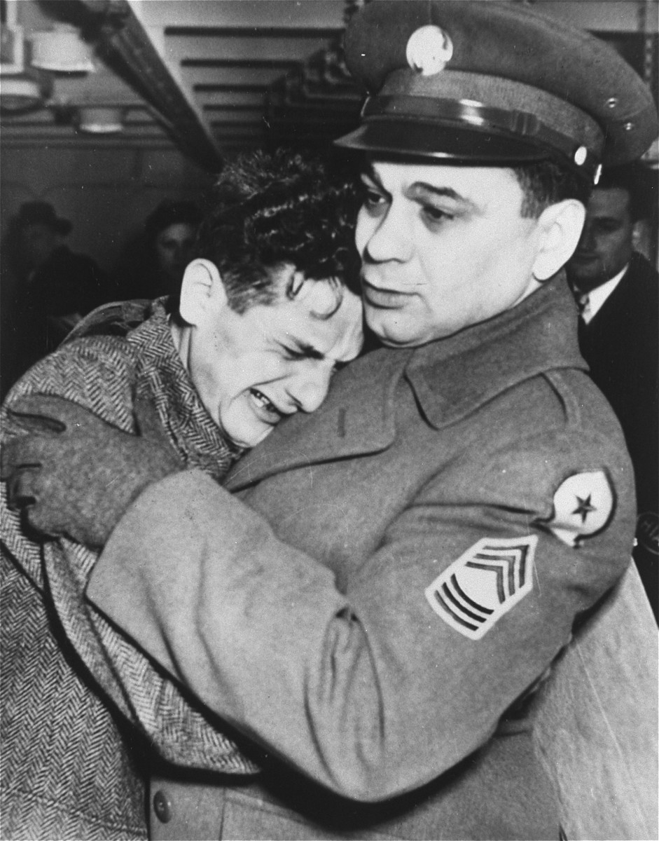 American serviceman Sergeant William Best greets 19 year-old Josef Guttman, a survivor of Buchenwald, whom Sgt. Best has adopted. After liberation Guttman became the mascot of the tank detachment Sgt. Best commanded.