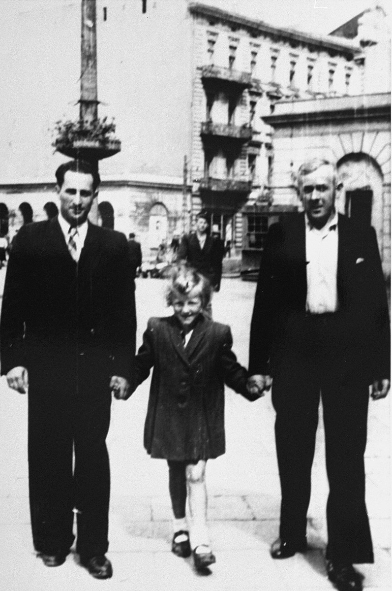 Guta Tyrangiel poses in the street with her uncle, Meyer Tyrangiel, and her rescuer and adopted father, Josef Jaszczuk.