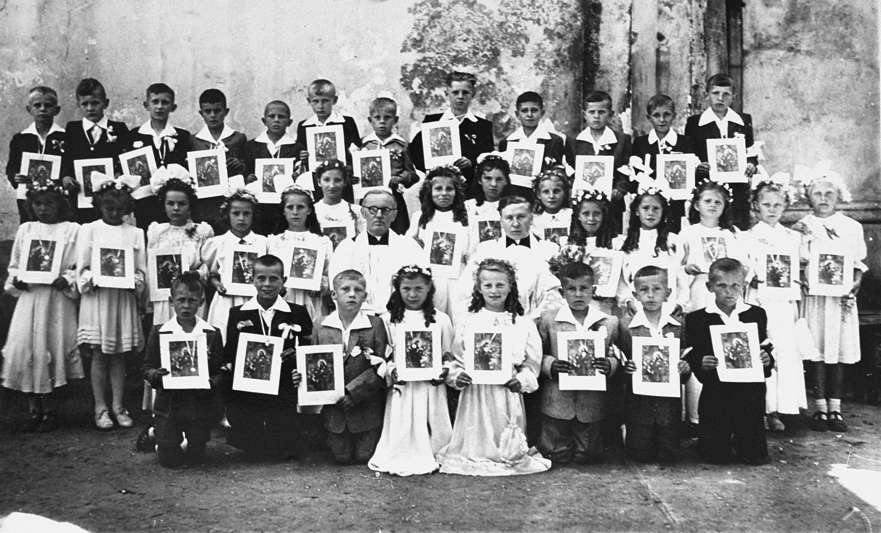 Group portrait of Polish children at their first communion holding pictures of Jesus.  Among them is Guta Tyrangiel, a Jewish child who had survived the war in hiding with a Polish family.