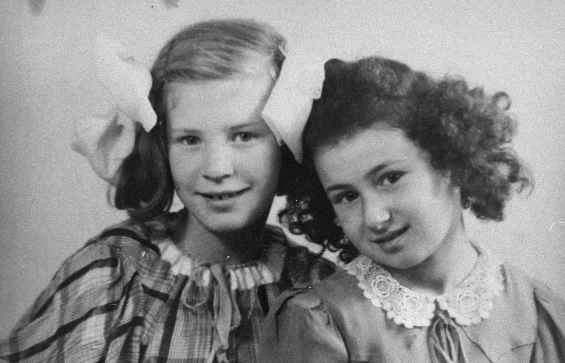 Marion Kaufmann with Rie Beelen, the daughter of her rescuers.  Both girls are wearing ribbons and dresses sewn from a retrieved Canadian parachute.