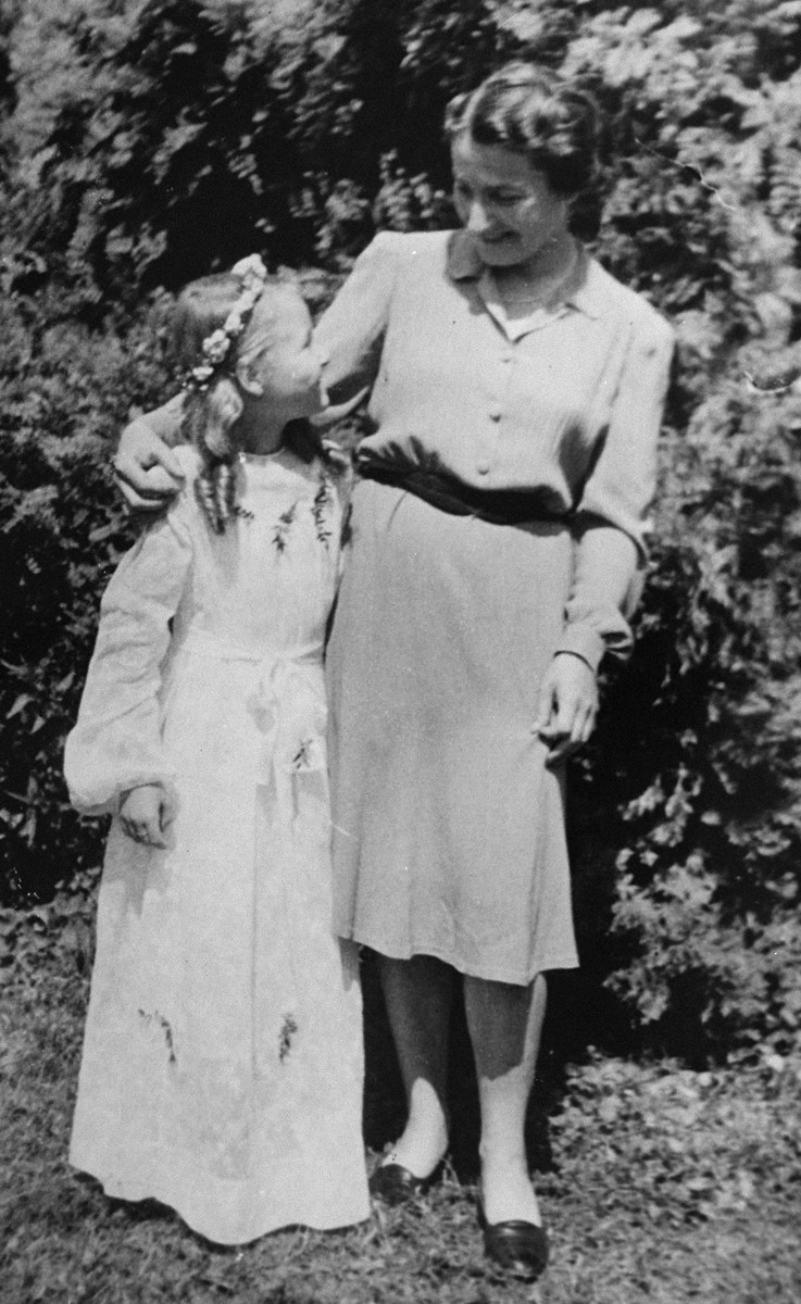 A Jewish mother poses with her daughter who is dressed for her First Communion.  Pictured are Laura Schwarzwald and her daughter Selma, who had lived in hiding as Polish Catholics during the war.