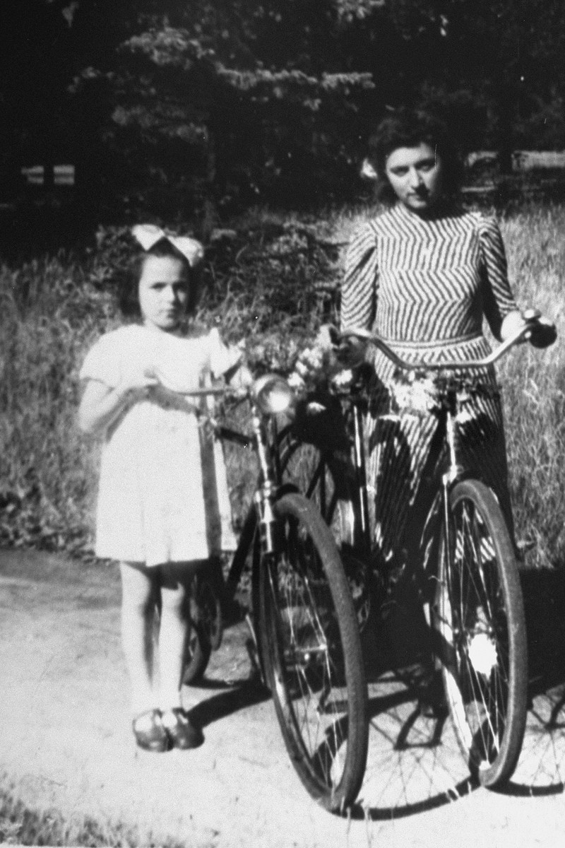 Anita poses with her bicycle after the war with a cousin of her rescuer, Father Kujata.