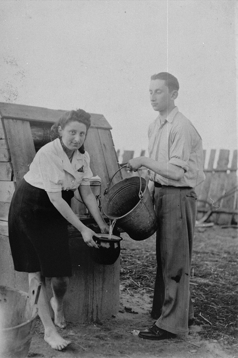 Sylvia Kramarski and Henry Leshno pump water on the Pawlak family farm in Krushev.   They were hidden,  together with Sylvia's father and other Jews in an underground bunker on the farm.  The Pawlaks (who were ethnic Germans) were paid for hiding them.  Sylvia stated that Mrs. Pawlak assisted her in baking Matzot in the middle of the night for Passover.