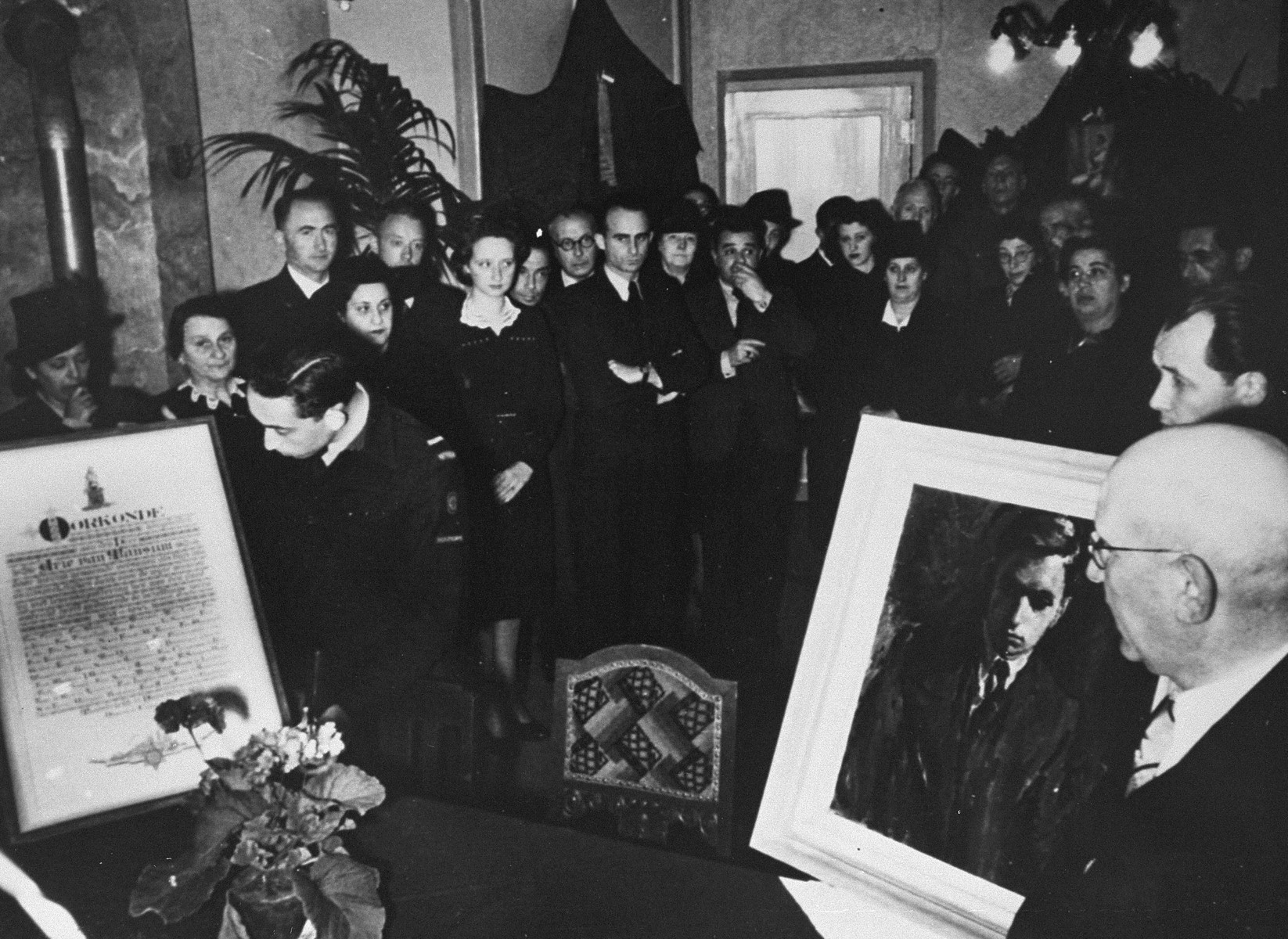 At a postwar ceremony in Holland, Jews who were rescued by Arie van Mansum during the German occupation, present him with a portrait and a certificate listing the names of those he saved.